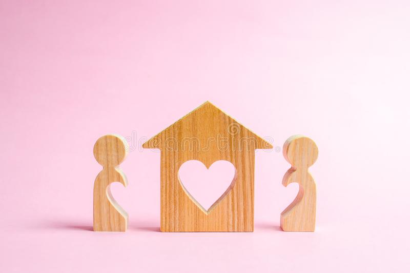A house with a heart stands between a pair of lovers. The concept of finding a love nest. Affordable housing for young families royalty free stock photography