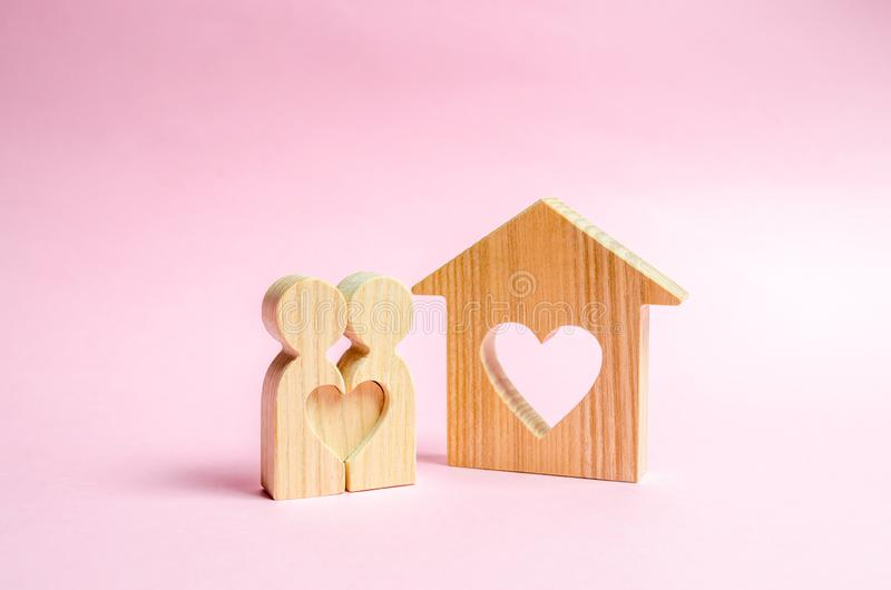 A house with a heart stands between a pair of lovers. The concept of finding a love nest. Mortgage, purchase credit. stock photos