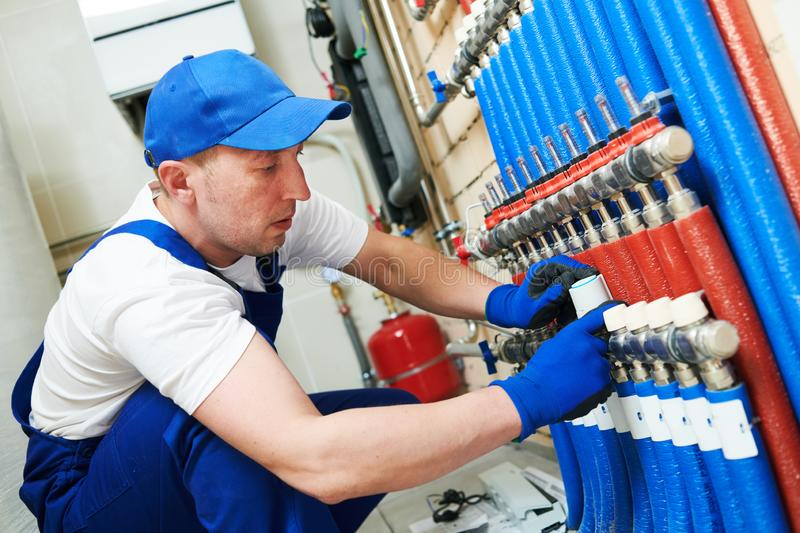 Plumber work. Installing collector for warm water underfloor heating system. House heating. installer plumber mounting control system collector for internal warm royalty free stock image