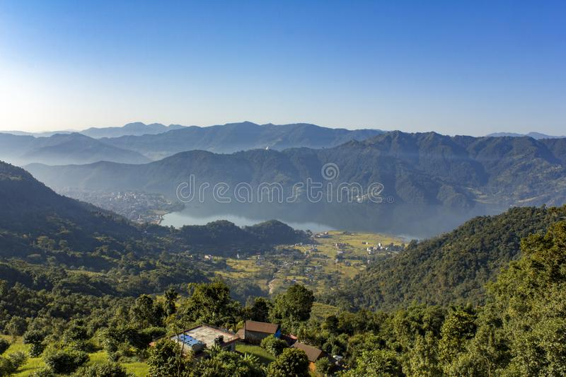 House on a hill, against the background of the city of Pokhara in a mountain foggy morning valley with Phewa lake under a clear stock images