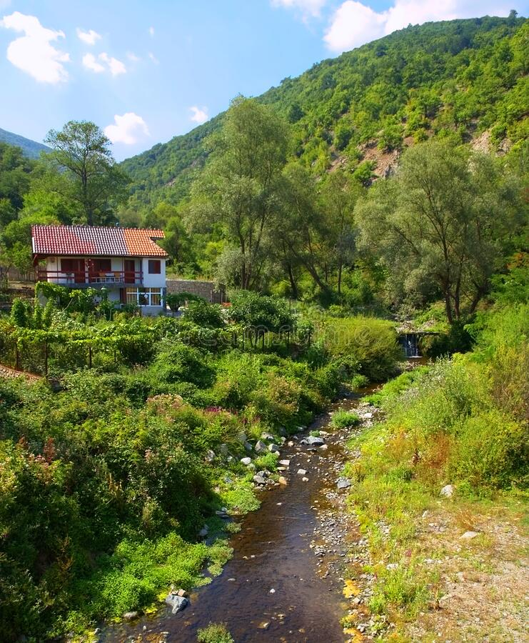 Small house on top of a hill and a river flowing by. House on a hill on the river side, green forest, landscape - summer stock photos