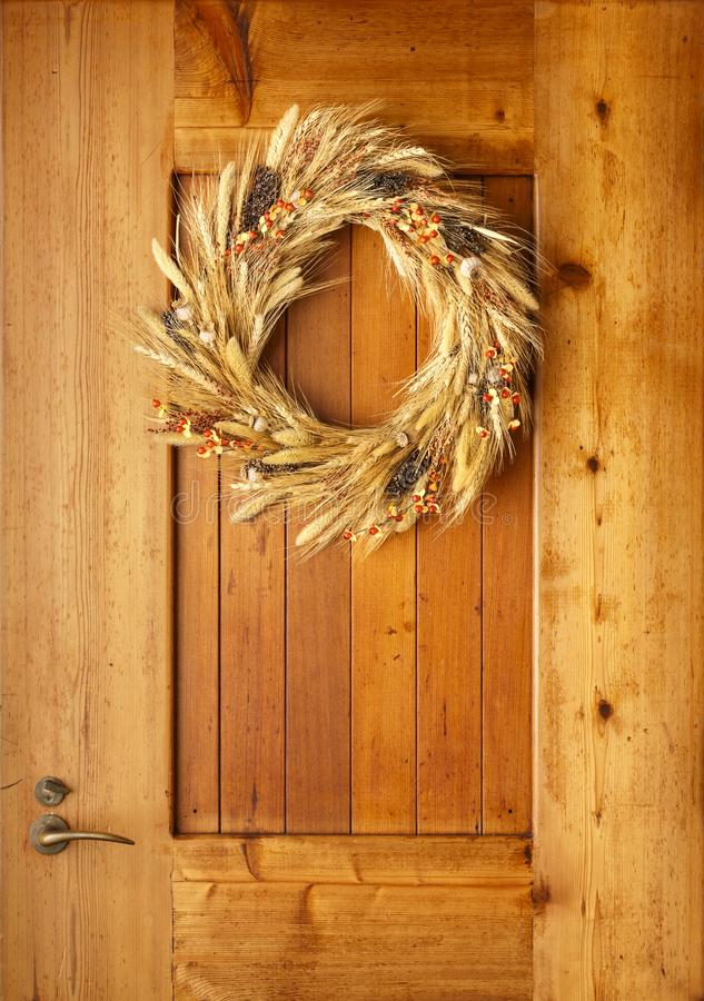 House home front door Fall autumn Thanksgiving decorations country style natural botanical rustic wreath on wood background royalty free stock images