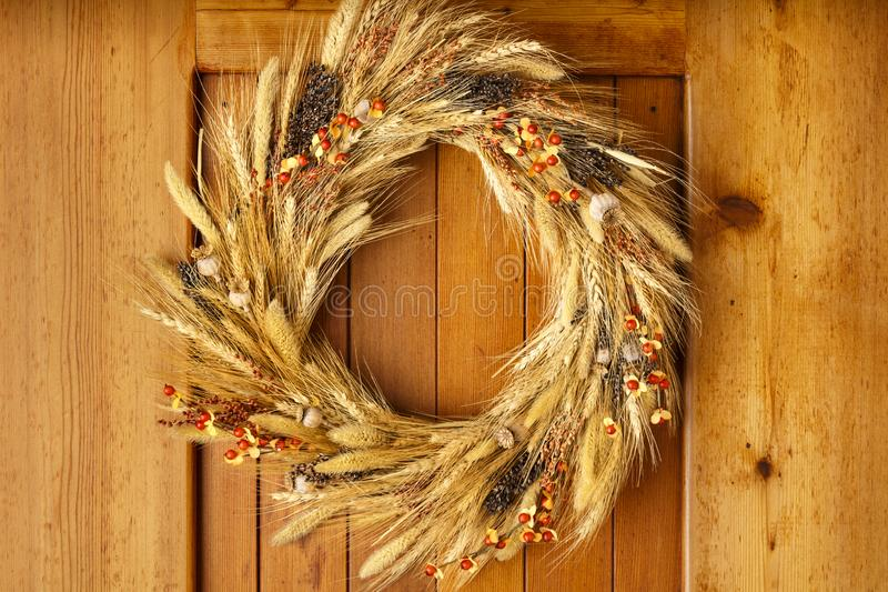 House home front door Fall autumn Thanksgiving decorations country style natural botanical rustic wreath on wood background royalty free stock photography
