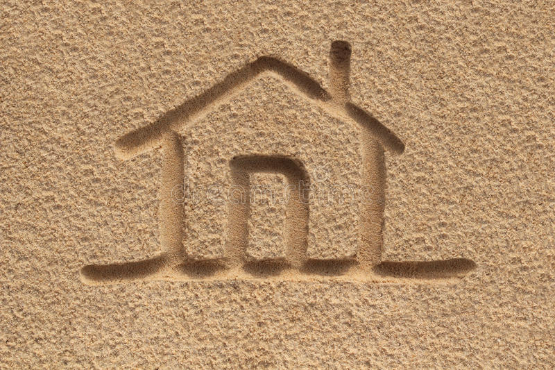 House(home) icon or sign drawing in beach sand - concept photo. This photo shows a hand written home symbol with door and roof drawn on the sand of a sea shore royalty free stock photos