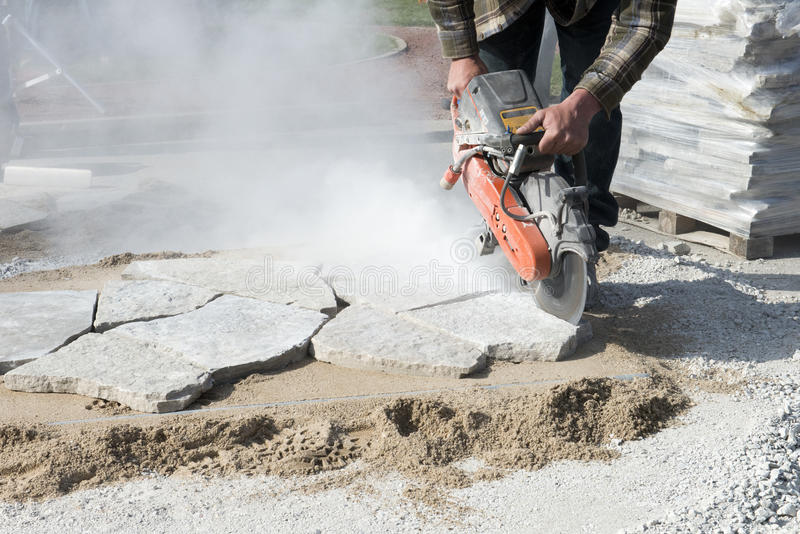 House or Home Improvement, Stone Cutting Patio Landscaping. A worker is cutting landscaping stone while he builds a patio for a house or home improvement project stock photos