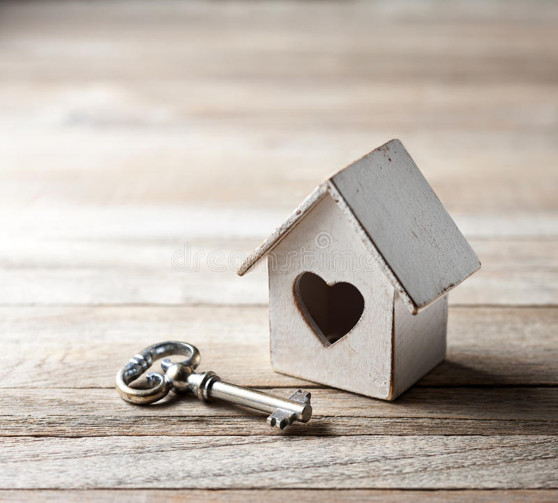 House Home Key Love Real Estate Success Background. A house with a heart and an old key on a rustic wood background stock photo