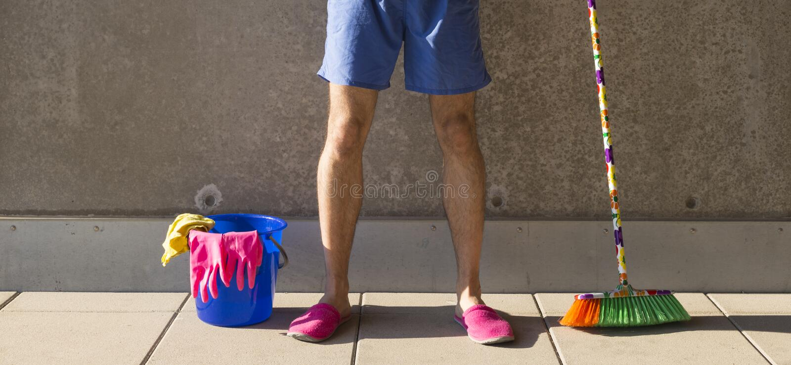 House husband in pink slippers cleaning the floor royalty free stock image