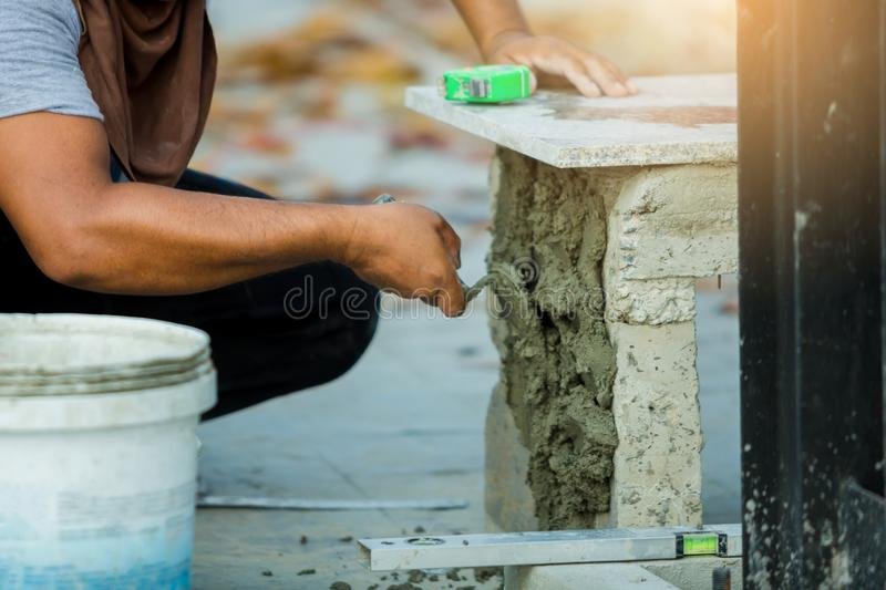 House improvement, renovation, construction industry worker installing granite stone tiles with cement. On architectural house royalty free stock image