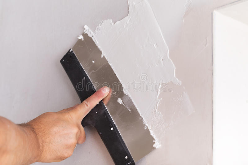 House improvement worker puts finishing layer of stucco on wall stock images