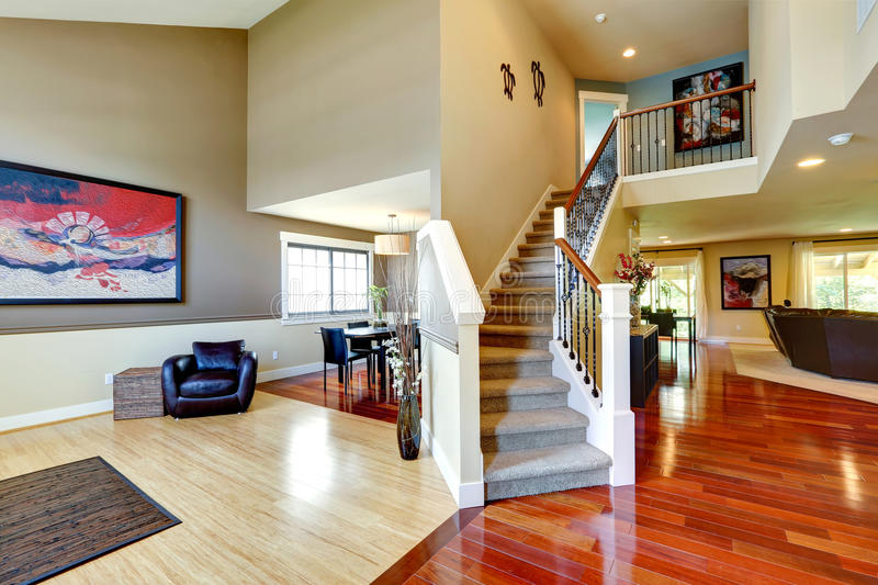 House interior. Hallway with classic staircase. House interior. Entrance hallway with contrast hardwood floor and carpet covered staircase royalty free stock photography