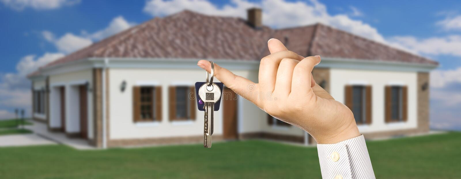 House key. Woman holding a key for a house on a keychain, house in background stock photos