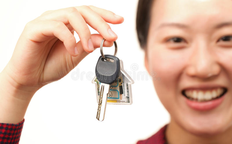 House key. Attractive young woman with a house key stock photos