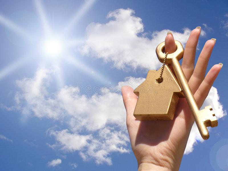 House Key. A hand holds up a huge golden key attached to a keychain in the shape of a house stock images