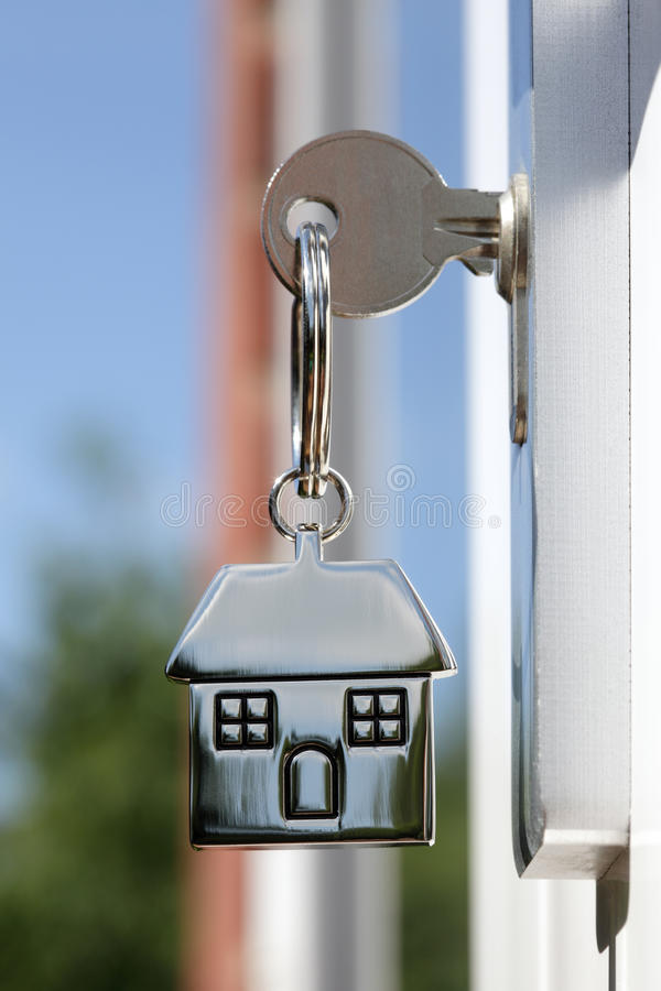 House key in the door. House key on a house shaped silver keyring in the lock of a door royalty free stock photos