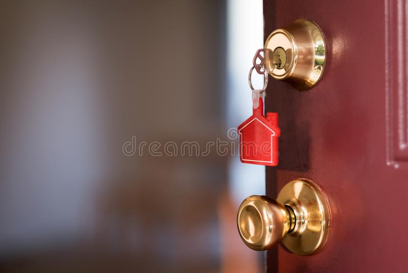House key in the door opening into apartment. House key with house shape keychain in the door stock photo