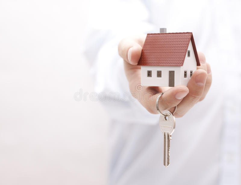 House key in hand. Small model house with key in hand stock images