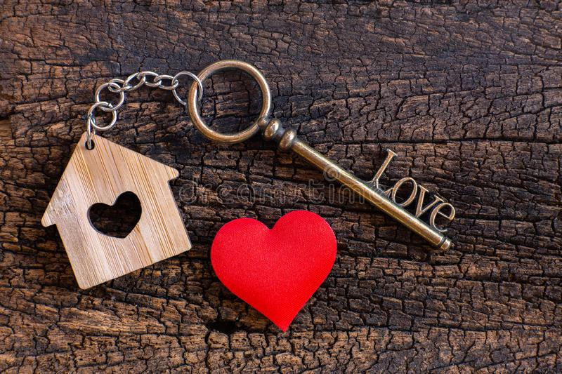 House key in heart shape with home keyring on old wood background decorated with mini heart. Home sweet home concept, copy space love valentine passion royalty free stock photography