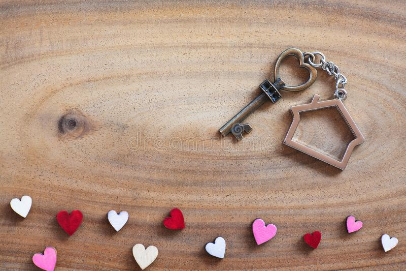 House key in heart shape with home keyring on old wood background decorated with mini heart. Home sweet home concept, copy space love valentine passion royalty free stock photos