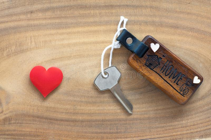 House key in heart shape with home keyring on old wood background decorated with mini heart. Home sweet home concept, copy space love valentine passion royalty free stock photo