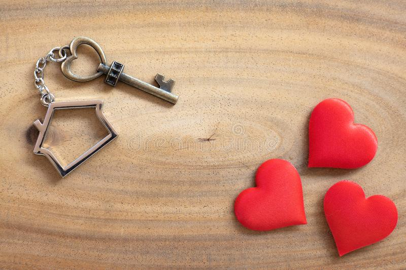 House key in heart shape with home keyring on old wood background decorated with mini heart. Home sweet home concept, copy space, love, valentine, passion royalty free stock images