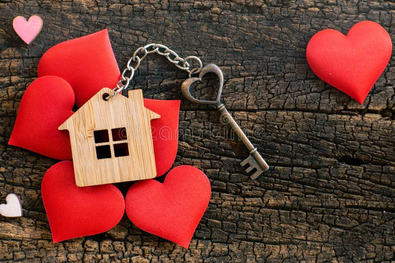 House key in heart shape with home keyring on old wood background decorated with mini heart. Home sweet home concept, copy space, love, valentine, passion royalty free stock photos