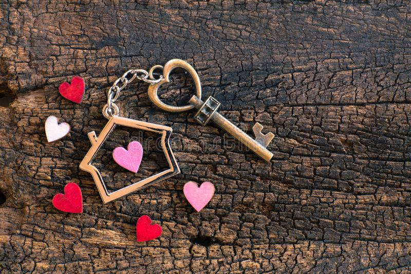 House key in heart shape with home keyring on old wood background decorated with mini heart. Home sweet home concept, copy space, love, valentine, passion stock photo
