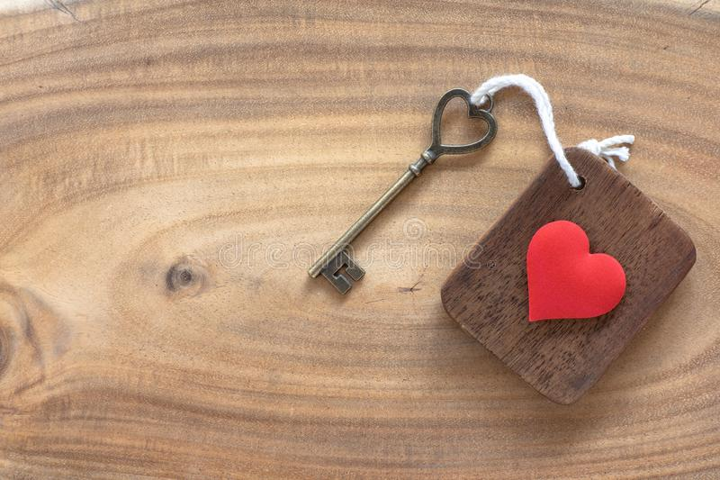 House key in heart shape with home keyring on old wood background decorated with mini heart. Home sweet home concept, copy space, love, valentine, passion royalty free stock photography