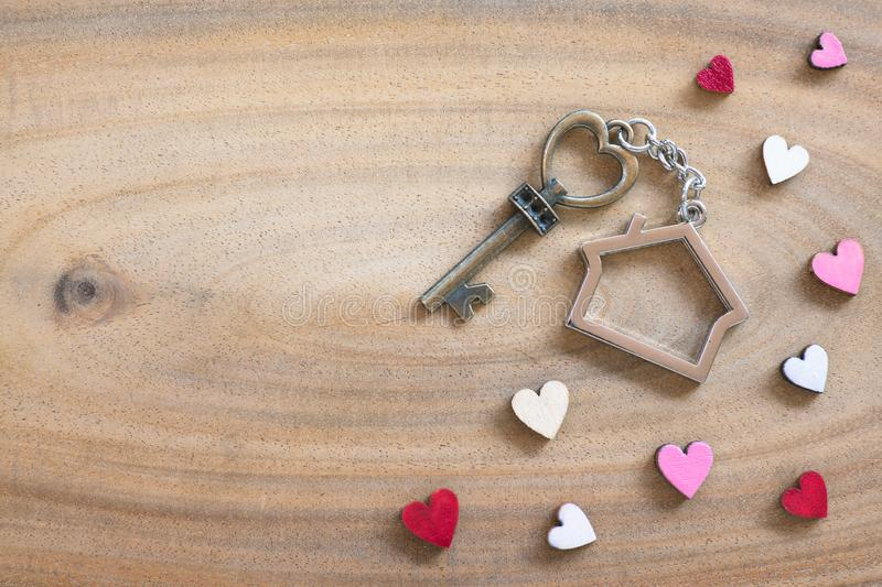 House key in heart shape with home keyring on wood background decorated with mini hearts. Copy space love valentine passion notebook text wooden texture stock image