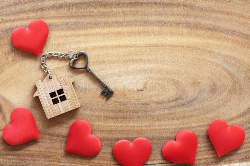 House key in heart shape with home keyring on wood background decorated with mini hearts. Copy space love valentine passion notebook text wooden texture stock photography