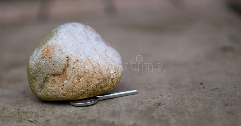 House key. Hidden under a rock stock image