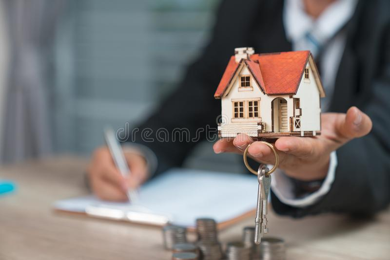 House key in home insurance broker agent`s hand protection or in. Salesman person giving to buyer customer stock photo