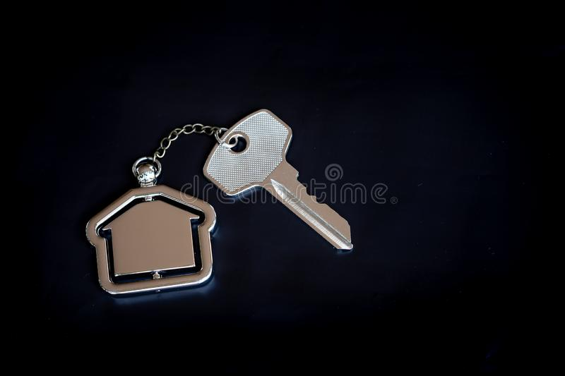 House key with home keyring in on black background. Real estate concept, copy space, unique, open, chain, antique, door, lock, owner, keyhole, safe, apartment stock image