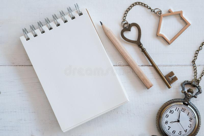 House key with home keyring, blank notebook and pencil on white wood table background. Copy space chain antique owner keyhole concept family figure property royalty free stock photography