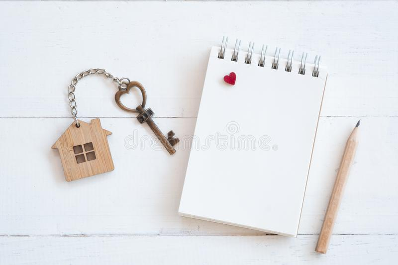 House key with home keyring, blank notebook and pencil on white wood table background. Copy space chain antique owner keyhole concept family figure property royalty free stock photo