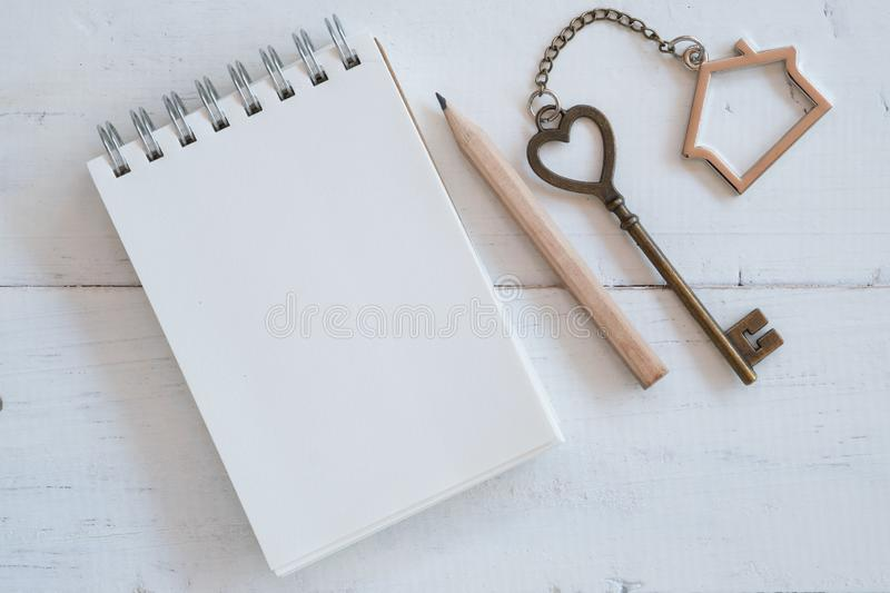 House key with home keyring, blank notebook and pencil on white wood table background. Copy space chain antique owner keyhole concept family figure property stock image