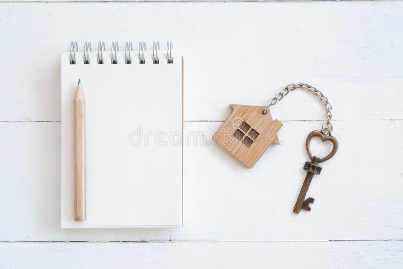 House key with home keyring, blank notebook and pencil on white wood table background. Copy space, chain, antique, owner, keyhole, concept, family, figure stock photo