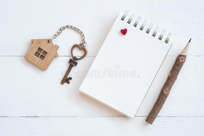 House key with home keyring, blank notebook and pencil on white wood table background. Copy space, chain, antique, owner, keyhole, concept, family, figure royalty free stock photography
