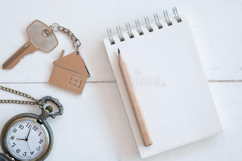 House key with home keyring, blank notebook and pencil on white wood table background. Copy space, chain, antique, owner, keyhole, concept, family, figure royalty free stock photo