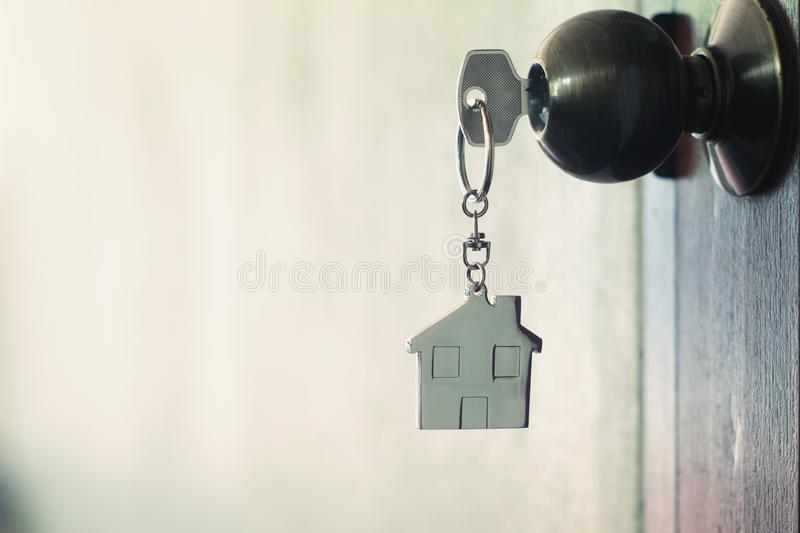 House key with home keyring in keyhole. On wood door, copy space unique open chain antique lock owner safe apartment secure concept image family front hotel royalty free stock photos