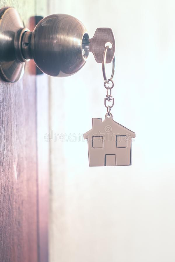 House key with home keyring in keyhole. On wood door, copy space, unique, open, chain, antique, lock, owner, safe, apartment, secure, concept, image, family royalty free stock photography