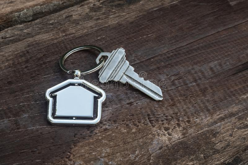 House key with home keyring in on old wood background. Copy space, unique, open, chain, antique, door, lock, owner, keyhole, safe, apartment, secure, concept stock images
