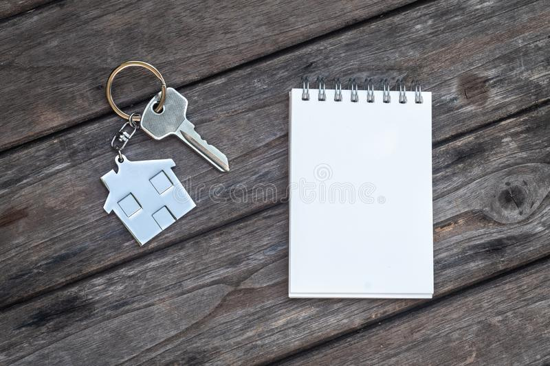 House key with home keyring in on old wood background. House key with home keyring and note paper in on old wood background, copy space, unique, open, chain royalty free stock images