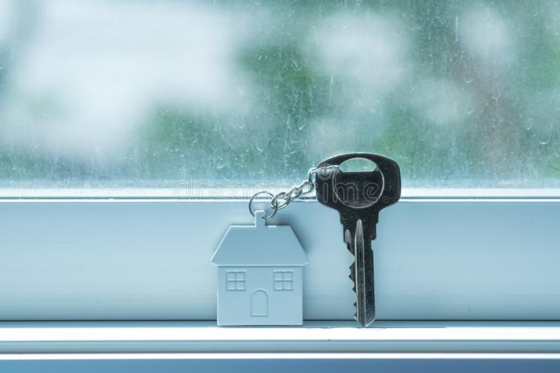 House key with home keyring on window background. Copy space, room, mirror, keychain, property, real, estate, dirty, white, single, lonely, alone, lock stock photo