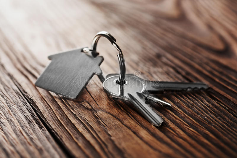 House key on house shaped keychain on wooden floorboards. House key on house shaped keychain wooden floorboards royalty free stock photos