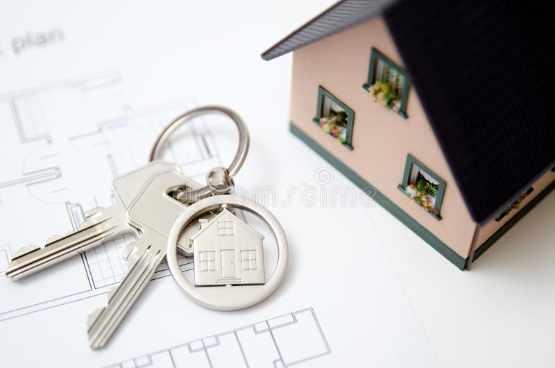 House key on a house shaped pendant. stock images