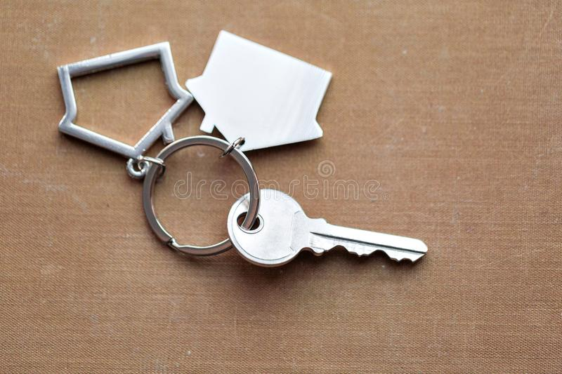 House key and keychain in the form of homes lies on fabric. Concept for real estate, mortgage, moving home or renting. House key and keychain in the form of royalty free stock photos