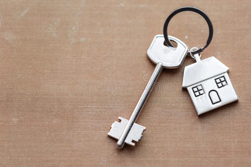 House key and keychain in the form of homes lies on fabric. Concept for real estate, mortgage, moving home or renting. House key and keychain in the form of stock photography