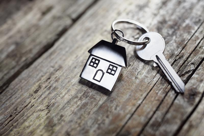 House key on keychain. House key on a house shaped keychain resting on wooden floorboards concept for real estate, moving home or renting property royalty free stock photo