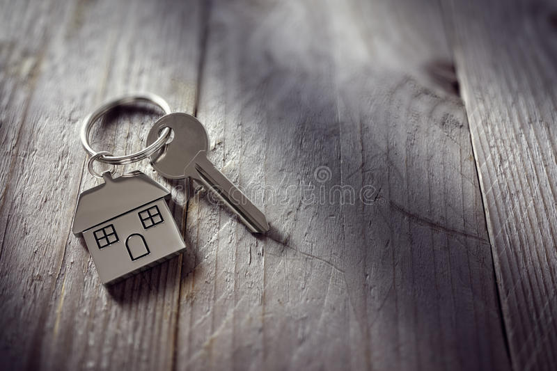 House key on keychain. House key on a house shaped keychain resting on wooden floorboards concept for real estate, moving home or renting property stock images