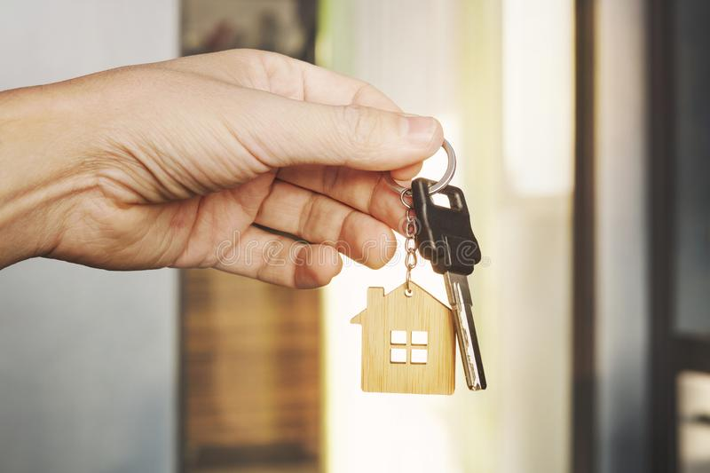 House key in male hand at apartment background. house key ring. Concept of moving in new living apartment. Symbol of purchasing royalty free stock photography